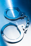 Closed handcuffs on a metallic background with dramatic lighting Royalty Free Stock Images