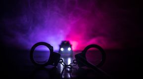 Closed handcuffs on the street pavement at night with police car lights. Police raid at night and you are under arrest concept. Silhouette of handcuffs with Stock Photos