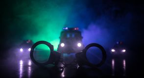 Closed handcuffs on the street pavement at night with police car lights. Police raid at night and you are under arrest concept. Silhouette of handcuffs with royalty free stock images