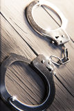 Closed handcuffs on a wooden background Royalty Free Stock Photography