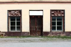 Closed hardware store front with two windows and locked doors with cracked paint mounted on dilapidated broken facade. With road and gravel in front royalty free stock photo