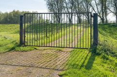 Closed iron gate in a rural landscape Stock Image