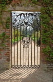 A Closed Iron Gate. With the view of the garden beyond and the design showing in the shadows Royalty Free Stock Photography