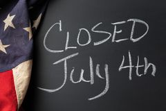 Closed July 4th Sign. Handwritten on a chalkboard bordered by a vintage American flag Stock Photos