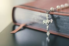 A closed leather bible sits on a table with a crucifix. Stock Photography
