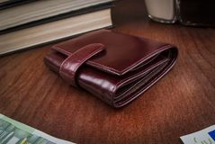 Closed leather men`s wallet. On the table Stock Photography