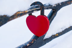 A closed lock in the shape of a red heart on a background of  metal Royalty Free Stock Photography