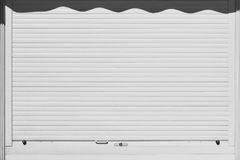 Closed and locked white rolling shutter. Security background. Royalty Free Stock Photos