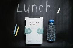 Closed lunch box with a cute muzzle and a bottle of water on a black background with colored crayons and the inscription lunch. Written in white chalk royalty free stock image