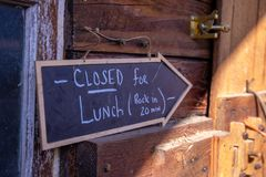 `Closed for lunch` sign at a barn wall royalty free stock images