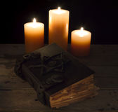 Closed magic book with candles. Halloween still life with closed magic book and candles on the table Royalty Free Stock Image