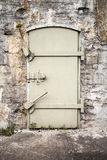 Closed massive metal door in old wall Royalty Free Stock Image