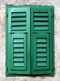 Closed mediterranean window. Closed mediterranean green wooden window on a ruff wall Royalty Free Stock Photography