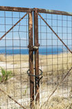 Closed metal gate on the background of the sea Royalty Free Stock Photo