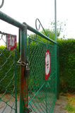 Closed metal gate. Padlocked metal gate with a road sign Royalty Free Stock Photography