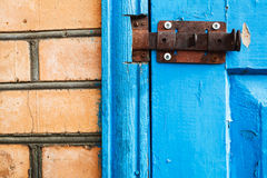Closed metal latch on blue painted woooden door Stock Photos