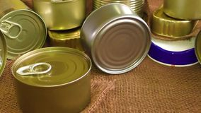Closed metal tin cans on brown background stock video