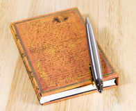 Closed notebook with pen. Hardcover notebook with silver ballpoint arranged on wooden background Stock Photo