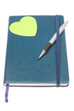Closed notebook with a pen and a green heart. Royalty Free Stock Photo