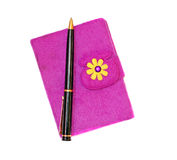 Closed notebook in a purple cover with a black ballpoint pen on Stock Image