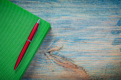 Closed notepad ball-point pen on wooden board top view office co Royalty Free Stock Photography
