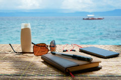 Closed notepad, sunglasses phone with headphones and white tube of cream solar protect on the table against philippine Stock Image
