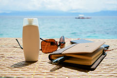 Closed notepad, sunglasses phone with headphones and white tube of cream solar protect on the table against philippine Royalty Free Stock Images