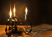 Closed old book and three burning candles in the candlestick Stock Photo