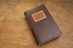 Closed Old Book on a Wooden Table Royalty Free Stock Photography