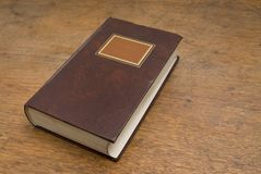 Closed Old Book on a Wooden Table Royalty Free Stock Image