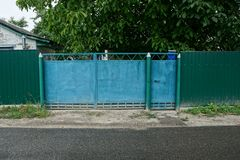 Closed old iron gate of green color and fence near the road on the street. Closed old iron gate of green color and a fence near the asphalt road in the street stock photos