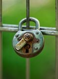 A closed old rusty lock. A close up on a green background stock images