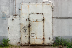 Closed old white metal door in an industrial building Royalty Free Stock Photos
