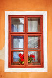 Closed old window with red flowers in orange wall Royalty Free Stock Images