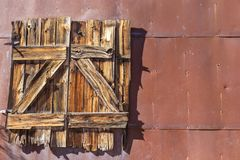 Closed Old Wood Window on Metal Wall of Abandoned House. Obsolete Old Wooden Window Closed on Metal Wall of Abandoned House Stock Images