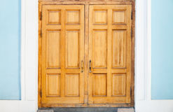 Closed old wooden door in blue white wall Royalty Free Stock Photo