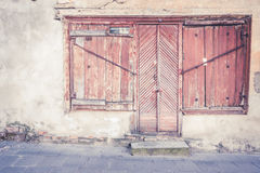 Closed old wooden door and windows with wooden shutters in abandoned building Stock Photo