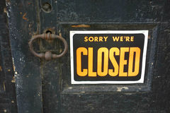 Closed. An orange sign saying Sorry We're Closed on an old door Stock Photos