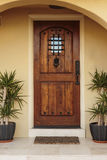 Closed Ornate Front Door of an Upscale Stucco House. Closed ornate wood door of an upscale home, accented with an iron barred window, iron door knocker, and iron Stock Image