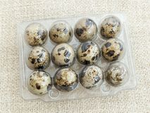 Closed package with twelve spotted quail eggs in a transparent plastic packaging. A dozen raw quail eggs on a beige textile royalty free stock image