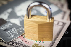 Closed padlock over a stack of money and cards Stock Images