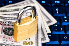 Closed padlock over a stack of money on a keyboard Stock Photo