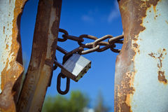 Closed padlock in the sky. Closed rusty padlock on a chain on a background of blue sky stock image