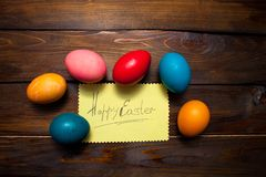 Closed, painted in different bright colors chicken eggs for the holiday Easter on natural wooden background with sheet of paper an. D the inscription Happy royalty free stock photography