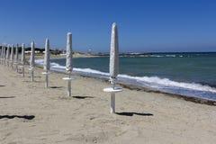 Closed parasols on the beach Stock Photos