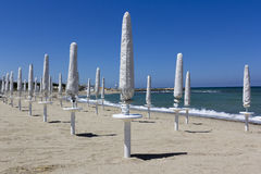 Closed parasols on the beach Royalty Free Stock Photo