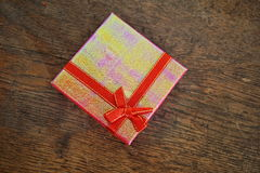 Closed pink gift box with red ribbon and golden stitching on the wooden background as a symbol of giving and getting gifts Stock Images