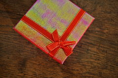 Closed pink gift box with red ribbon and golden stitching on the wooden background as a symbol of giving and getting gifts Stock Photos