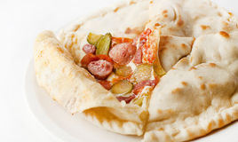 Closed pizza with Bavarian sausages and pickles Stock Images