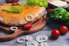 Closed pizza calzone on a light wooden background Royalty Free Stock Photos